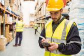Focused worker wearing yellow vest using handheld — Stock Photo