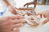 Hands of business people taking doughnut — Stock Photo