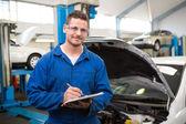 Smiling mechanic writing on clipboard  — Stock Photo