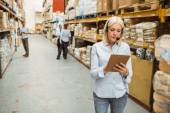 Focused warehouse manager writing on clipboard — Stock Photo
