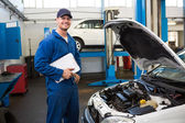 Smiling mechanic holding a clipboard — Stock Photo