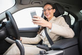 Smiling businesswoman sending a text message — Stock Photo