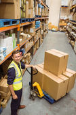 Worker with trolley of boxes smiling at camera — Stock Photo