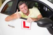 Man gesturing thumbs up holding a learner driver sign — Stock Photo
