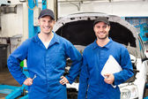 Team of mechanics smiling at camera — Stock Photo