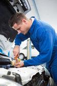 Mechanic using screwdriver on engine — Stock Photo