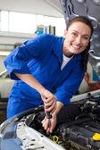 Smiling mechanic working under the bonnet — Stock Photo