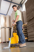 Focused man moping warehouse floor — Stockfoto