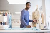 Smiling university student measuring waist of model — Stock Photo
