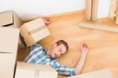 Man lying under fallen boxes — Stock Photo
