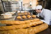 Baker checking freshly baked bread — Stock Photo