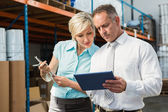 Warehouse managers looking at tablet pc — Stock Photo