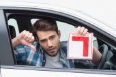 Learner driver smiling and holding l plate — Stock Photo