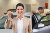 Saleswoman showing customer car key — Stock Photo