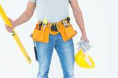 Repairman holding spirit level and hardhat — Stock Photo