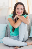 Pretty brunette sitting on the couch — Stock Photo