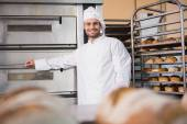 Baker leaning on professional oven — Stock Photo