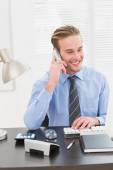 Smiling businessman working and phoning — Stock Photo