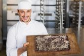Baker showing freshly baked brownie — Stock Photo