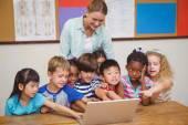 Insegnante e alunni guardando portatile — Foto Stock