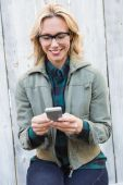 Blonde in glasses text messaging — Stock Photo
