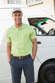 Smiling man in front of delivery van — Stock Photo