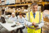 Smiling manager wearing yellow vest using handheld — Stock Photo