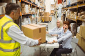 Manager wearing yellow vest giving box to his colleague — Stock Photo