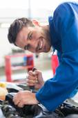 Mechanic using screwdriver on engine — Stock Photo