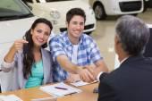 Venditore dando le chiavi della macchina per un paio — Foto Stock