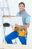 Electrician holding laptop by step ladder — Stock Photo