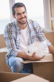 Smiling man unpacking cardboard boxes — Stock Photo