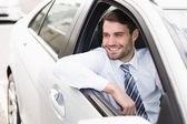 Happy businessman sitting in drivers seat — Stock Photo
