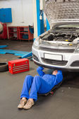 Mechanic lying and looking under car — Stock Photo