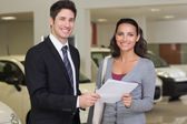 Salesperson showing clipboard to sign to customer — Stock Photo