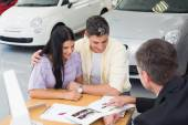 Salesperson pointing something on booklet — Stock Photo