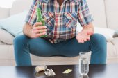 Man with beer and medicine laid — Stock Photo