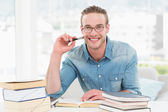 Smiling businessman studying at desk — Stock Photo