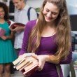 Student carrying small pile of books — Stock Photo #65560015