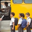 Cute schoolchildren waiting to get on school bus — Stock Photo #65560401