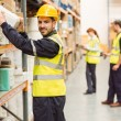 Smiling warehouse worker taking package in the shelf — Stock Photo #65560431
