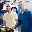 Mechanic showing customer the problem with car — Stock Photo #65561459