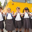 Cute schoolchildren smiling at camera by the school bus — Stock Photo #65561765