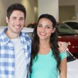 Smiling couple standing in front of a car — Stock Photo #65562407