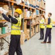 Warehouse worker taking package in the shelf — Stock Photo #65562659