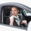 Businessman putting on his seat belt — Stock Photo #65563625