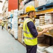 Warehouse worker taking package in the shelf — Stock Photo #65563769