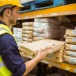 Warehouse worker taking package in the shelf — Stock Photo #65563807