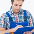 Plumber writing notes on clipboard — Stock Photo #65564673
