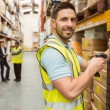 Warehouse worker scanning box while smiling at camera — Stock Photo #65565485